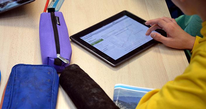 Ученик на уроке с планшетом. Архивное фото