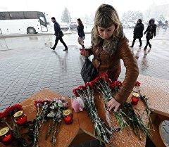Ростов-на-Донудагы авиакырсыктан каза болгондордун элесине аэропортто гүл коюп жаткан аял.
