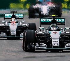 Слева направо: гонщик команды Мерседес Льюис Хэмилтон и гонщик команды Мерседес Нико Росберг принимают участие в гонке на российском этапе чемпионата мира по кольцевым автогонкам в классе Формула-1.