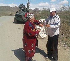 Местная жительница передает сумолок пограничнику