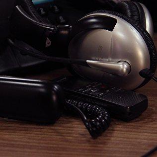 Наушники с микрофоном для аудизаписи и стационарный телефон на столе. Архивное фото