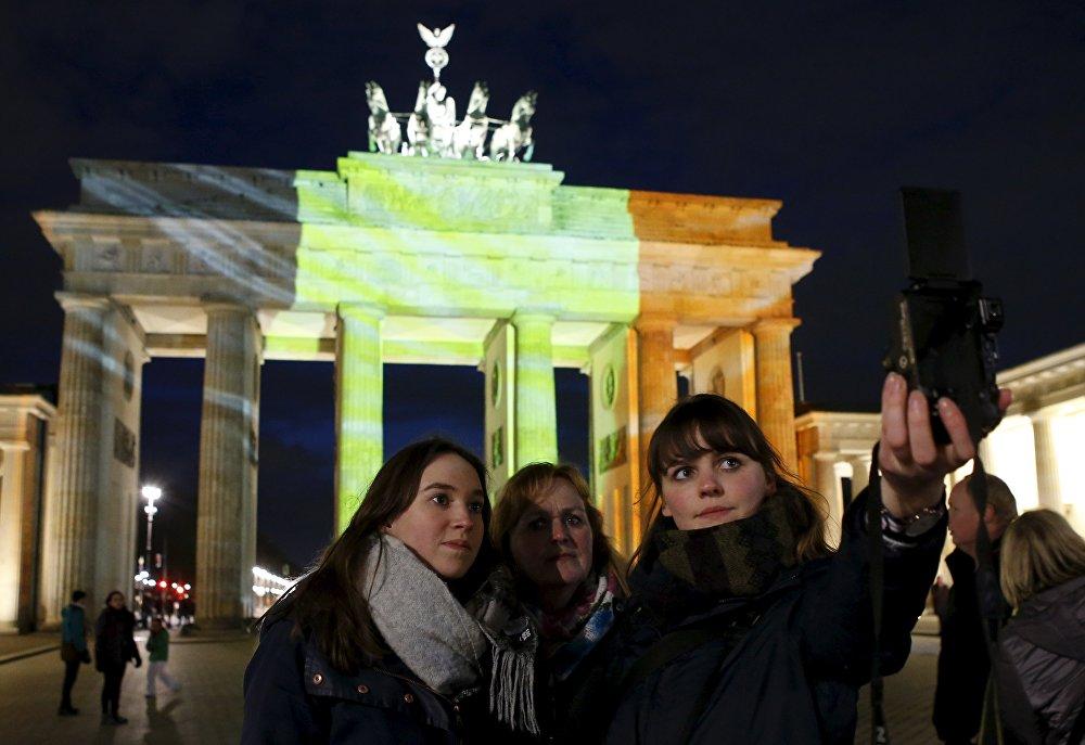 Берлиндин борборунда жайгашып, белгия байрагынын түсүнө боёлгон Бранденбургск дарбазасынын алдында кыздар селфи жасоодо