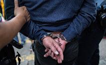 Задержанный мужчина в наручниках. Архивное фото