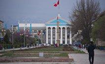 Люди идут по Аллее молодежи возле здания мэрии города Бишкек. Архивное фото