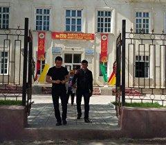 Избиратели выходят из избирательного участка в городе Майлуу-Суу
