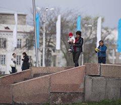 Бишкектин көчөлөрүндө бараткан аял балдары менен. Архивдик сүрөт