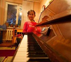 Алты жашар Малика белекке алган пианинонун жанында