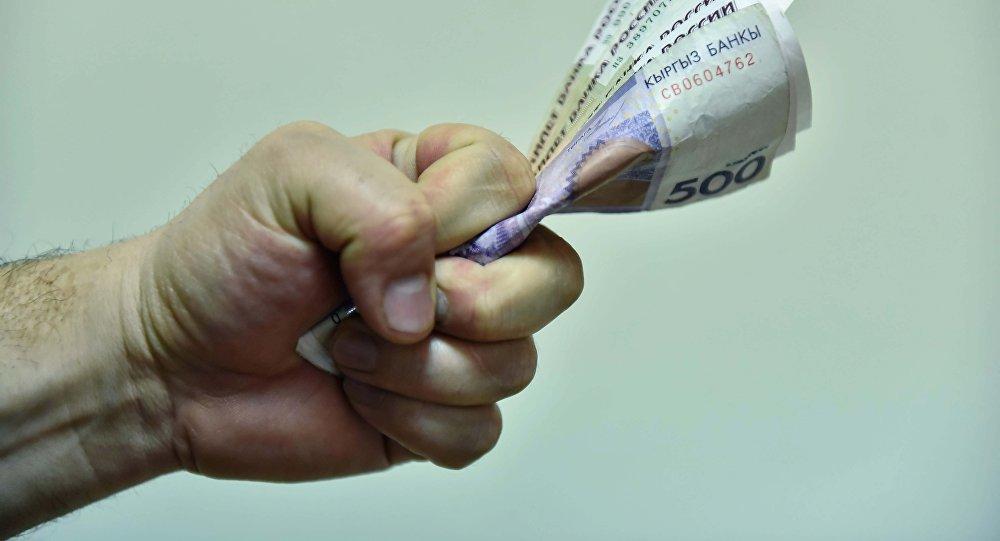 Мужчина в кулаке держит деньги. Архивное фото