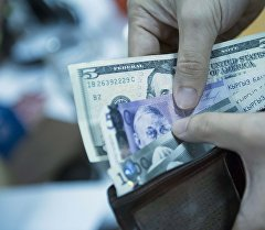 Архивное фото мужчины, который вытаскивает долларовые и сомовые купюры из портмоне