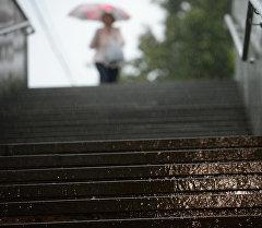 Женщина у лестницы подземного перехода во время сильного дождя. Архивное фото