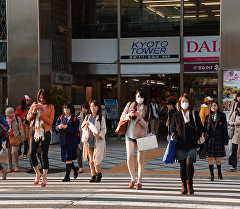 Люди с смартфонами в руках на пешеходном переходе. Архивное фото