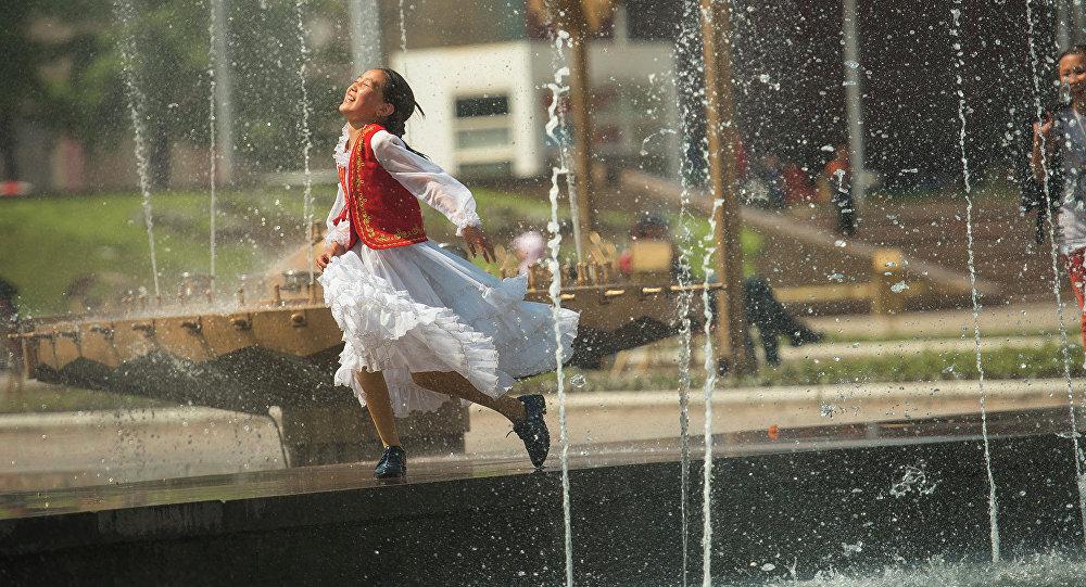Девочка играет у фонтана. Архивное фото