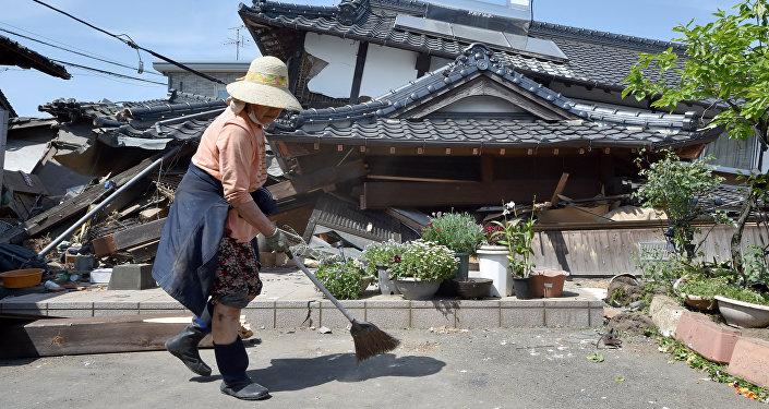 Житель в префектуре Кумамото на фоне разрушенных домов от землетрясений. Архивное фото