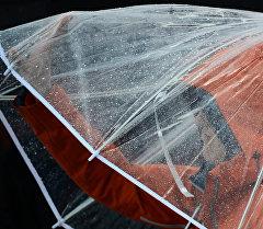 Мужчина с зонтом во время дождя. Архивное фото