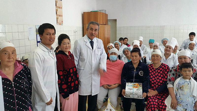 Хирург Калдарбек Абдраманов (в центре с галстуком) с коллегами и пациентами в больнице