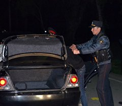 Курал-жарак табылган Toyota Alteza унаасы жана ичинен кармалган жарандар.