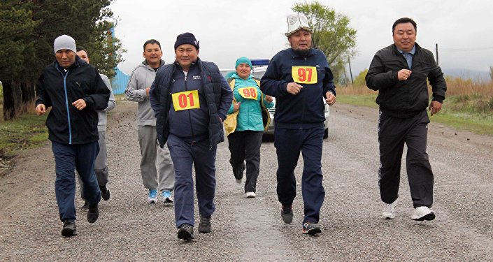 Полномочный представитель правительства в Иссык-Кульской области Асхат Акибаев с участниками марафонского забега в городе Каракол.