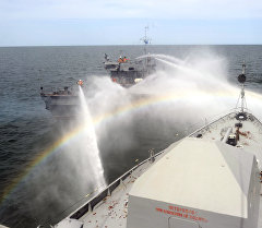 Пожарный катер поливает водой малый корабль. Архивное фото