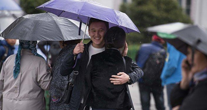 Пара под зонтиком во время дождливой погоды в Бишкеке. Архивное фото