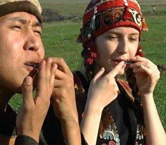 Темир комуз кагып, кыргыздын улуттук кийимин кийген биздин Катя