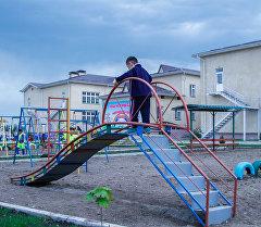 Мальчик играет на горке на детской площадке. Архивное фото