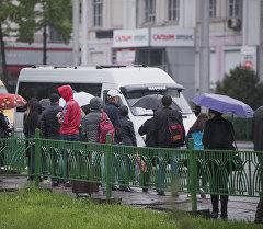 Люди у остановки во время дождя в Бишкеке. Архивное фото