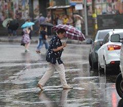 Женщина переходит дорогу во время дождя. Архивное фото