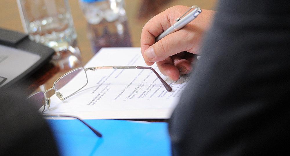 Мужчина держит ручку во время пресс-конференции. Архивное фото