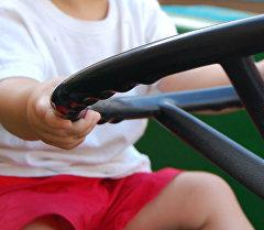 Ребенок за рулем игрушечной машинки. Архивное фото