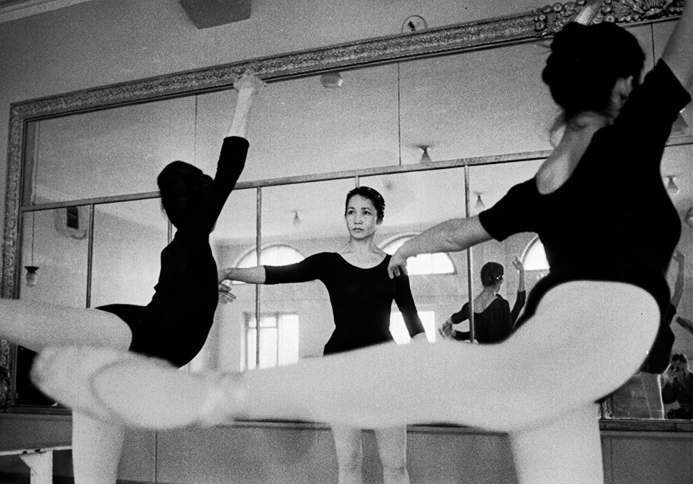 Балерина занимается с молодыми танцовщицами
