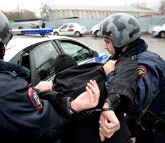 Полиция кызматкерлери кишини кармоосу. Архив