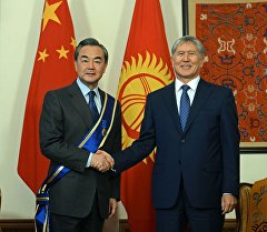 Президент Кыргызстана Алмазбек Атамбаев во время награждения министра иностранных дел Китая Ван И орденом Данакер