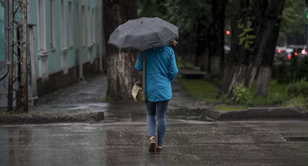 Архивное фото девушка переходящей улицу во время дождя