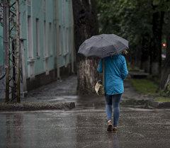 Девушка с зонтом переходит дорогу в Бишкеке. Архивное фото