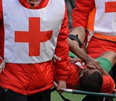 Медики на носилках уносят травмированного футболиста. Архивное фото