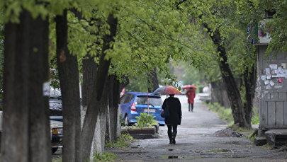 Женщина с зонтом на одной из улиц Бишкека. Архивное фото
