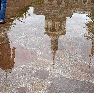 Отражение Международного Университета Кыргызстана на асфальте после дождя. Архивное фото