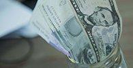 Сомовые и долларовые купюры положенные в банку. Архивное фото