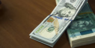 Пачка сто долларовых и пяти тысячных купюр на столе. Архивное фото
