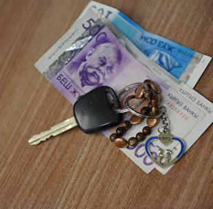 Автомобильный ключ с деньгами на столе. Архивное фото