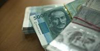 Кыргызская валюта номиналом в пять и одна тысячи сом на столе. Архивное фото