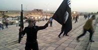 Ислам мамлекети террордук уюмунун желегин кармаган согушкер. Архив