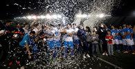 Футболисты с трофеем, после того, как играли футбольный матч 120-часовой, чтобы побить рекорд Гиннеса в Сантьяго.