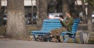 Женщина с телефоном на одном из аллей Бишкека. Архивное фото