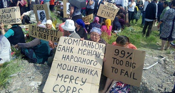 Они держат плакаты и лозунги, на которых написано Кто защитит права заемщиков?, Компаньон — банк международного мошенника Mercy Corps.