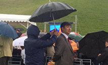 Чиновник, помощник которого держит над ним зонт