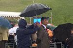 Прокурор Бишкека Нурлан Сулайманкулов помощник которого держит над ним зонт