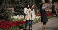 Девушки фотографируются у тюльпанов в Бишкеке. Архивное фото