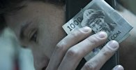 Мужчина держит сомовую валюту с мобильным телефоном. Архивное фото