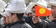 Молодой парень держит флаг Кыргызстана. Архивное фото